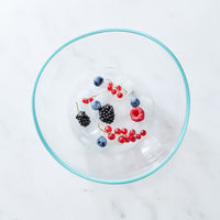 Glass bowl with different fresh berries and ice cubes on a gray marble background with space for text. Top view
