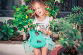 Portrait of a cute girl with ukulele