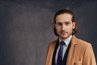 Handsome long-haired man in blazer and blue tie