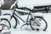 Old bike standing outdoors in the snow. Winter time, transportation and weather concept.