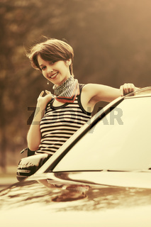 Happy young fashion woman with handbag leaning on her car