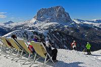Skifahrer sitzen im Liegestuhl auf der Dantercepies Aussichtsplattform vor dem Langkofel, Dolomiten