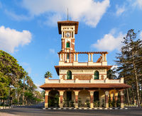 Clock tower in Montaza public park, decorated stone wall, green wooden window shutters, and red tile canopies, Alexandria, Egypt