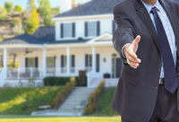 Male Agent Reaching for Hand Shake in Front of Beautiful New House
