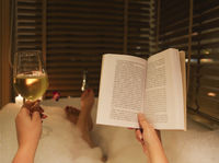 Young woman reading the book and drinking white wine in bath with foam and candles