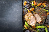 Barbecue marinated lamb roast with vegetable and potatoes as top view on a metal sheet with copy space left