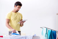 Handsome man husband doing clothing ironing at home