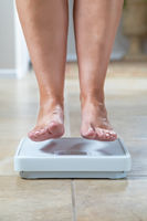 Woman Floating Slightly Above Sruface of Weight Scale