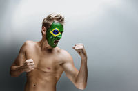 Emotional football fan with Brazil flag painted on his face over gray background