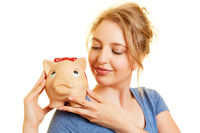 Frau schaut auf Sparschwein beim Geld sparen