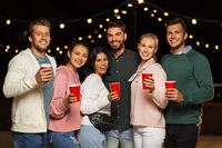 friends with party cups on rooftop at night