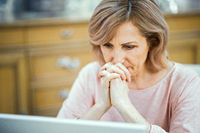 Concentrated woman stares pensively in the laptop