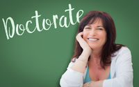 Doctorate Written On Green Chalkboard Behind Smiling Middle Aged Woman