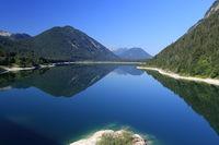 blauer spiegelnder See in den Alpen