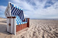 roofed wicker beach chair on baltic sea beach
