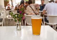 Pint of cool IPA on white table with flowers in Lisbon bar or cafe