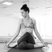 Fit sporty active girl in fashion sportswear doing yoga fitness exercise in yoga studio. Active urban lifestyle. Black and white image.