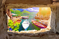 Limone sul Garda turquoise waterfront and boats view through stone window