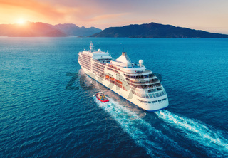 Aerial view of beautiful large white ship at sunset