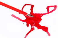 top view of red nib pen over red ink blot on white