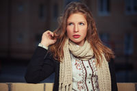 Young fashion girl in black cardigan and scarf in night city street