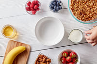 Ripe berries, granola, nuts, honey and an empty plate on a white wooden table. A woman's hand holds a glass of milk. Dietary food