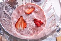 Freshly prepared strawberry smoothie in a blender bowl. Healthy food. Top view