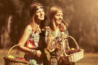 Happy teen girls with a fruit basket walking on nature