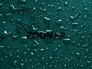 water drops on quetzal green colored metallic surface