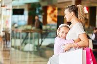 Kind umarmt ihre Mutter im Einkaufszentrum