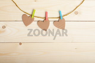 Handmade paper hearts hanging on clothesline over wood boards