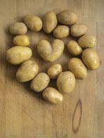 kartoffeln auf holztisch, eine kartoffel in form eines herzens