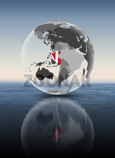 Peru on translucent globe above water