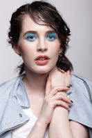 Portrait of female in blue jacket.Woman with unusual beauty makeup and wet hair, and blue shadows make-up.