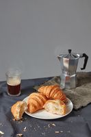 Continental breakfast with fresh croissant and natural coffee on a grey background.