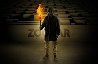 Man coming with burning flambeau from the maze concept
