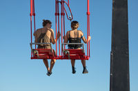 Young couple at swing at top of skyscraper in Amsterdam