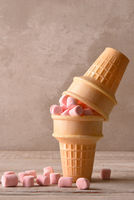Two ice cream cones with pink marshmallows