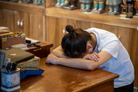 Tired chinese girl sleeping at the desk