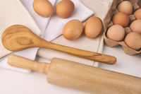 Overhead view of eggs, towels and kitchen tools on table