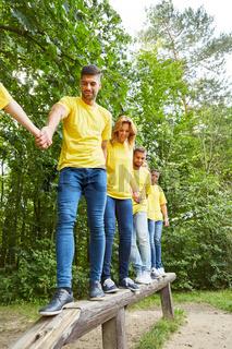 Mannschaft balanciert zusammen über einen Balken