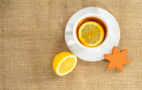 A cup of tea with slice of lemon and a half lemon and one star cookies.