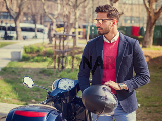 Trendy man by scooter in city