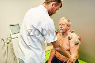 Orthopäde mit Senior Mann bei Elektrotherapie