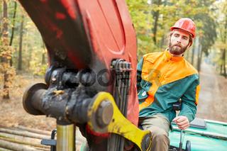 Waldarbeiter auf Forstkran von Forwarder im Wald