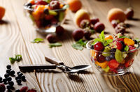 Assorted fruits in glass bowl on kitchen wooden table with spoon aside