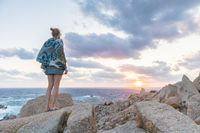 Solo young female traveler watches a beautiful sunset on spectacular rocks of Capo Testa, Sardinia, Italy, a popular summer traveling destination in Europe.