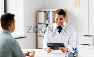 doctor with tablet computer and patient at clinic
