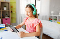 girl in headphones with tablet computer at home