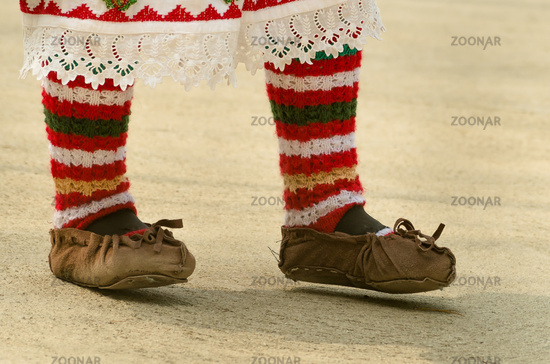 Girls dancing folk dance. People in traditional costumes dance Bulgarian folk dances. Close-up of female legs with traditional shoes, socks and costumes for folk dances.